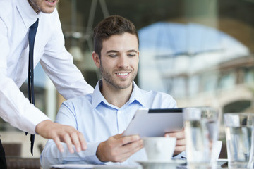 Businessman showing colleague how to use digital tablet