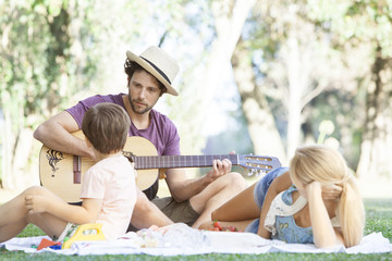 Man playing acoustic guitar for wife and son
