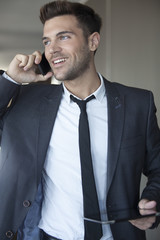Young businessman taking phone call on the move