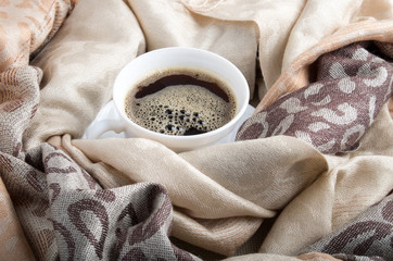 Cup of coffee in the folds of the female scarf