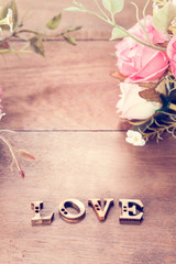 Word Love with rose flower on wood table, Valentine's Day background