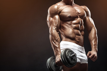 Muscular bodybuilder guy doing exercises with dumbbell Wall mural