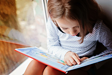 toddler girl with book