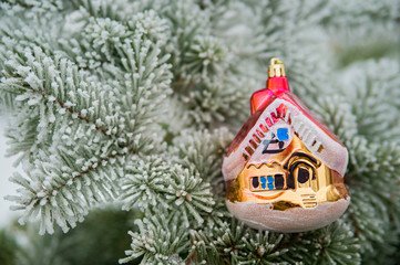 Glass toy house hanging on the branch of a pine. Needles covered