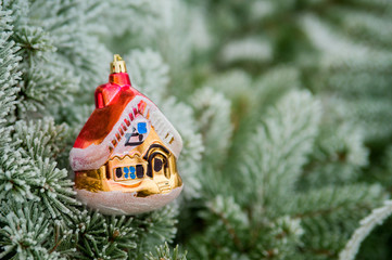 decorative toy house lies on a branch of a pine. Needles covered
