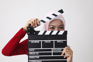 malay woman holding clapper board