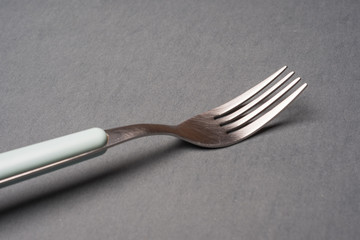 Still life of a fork on grey background