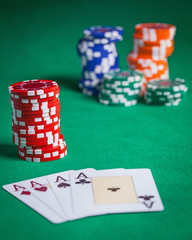 Red poker chips stacked on green table