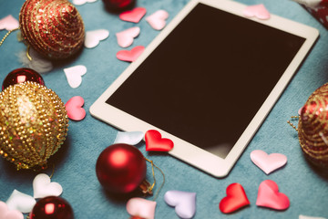 Festive blurry background with white tablet mobile computer, Christmas toys. Mock up view top image closeup