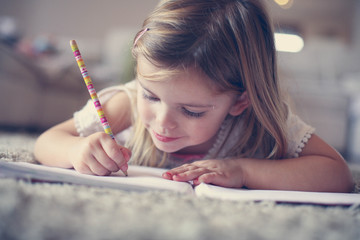 Little  girl writing  at home.