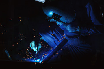 Welder of Metal Welding with sparks and smoke in factory