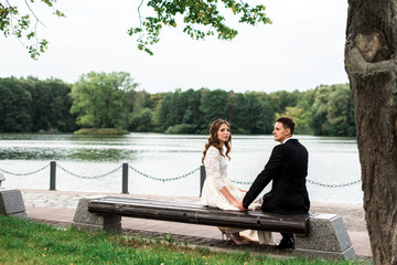 happy bride and groom at a park on their wedding day sitting on a bench near the lake