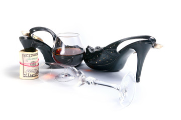 Women's high-heeled shoes, glasses of alcoholic drink, folded paper American dollars as a consequence of the party
