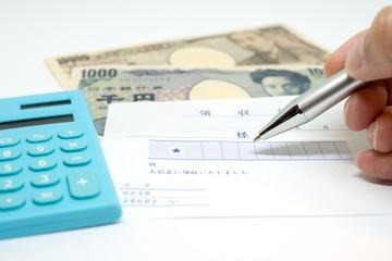 経費イメージ(領収書と電卓とお金、ボールペン)