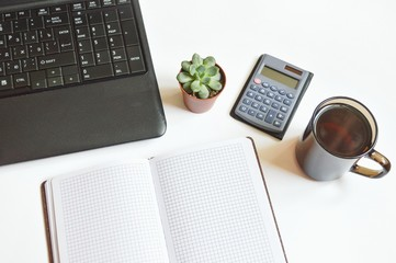 Economist or accountant workplace/ Laptop keyboard, open paper notebook, green succulent, calculator and mug of coffee. Workplace in office. Table accountant, economist or student