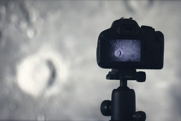 Moon photography. Camera with tripod capturing moon. Copernicus