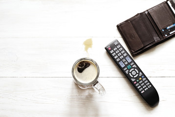 Beer glass, panel for the TV and a wallet on a white wooden surface