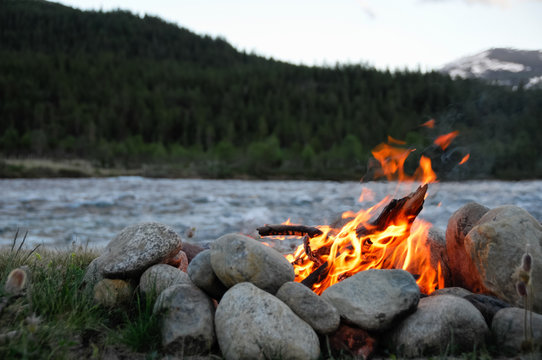 small campfire on the banks of a river between stones