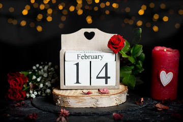 February 14 on cube calendar, red rose flower and candles, decor