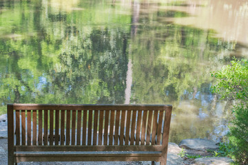 Peaceful sitting spot overlooking still, reflective water.  Bench.  Seat.