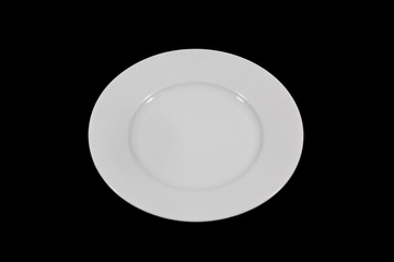 Flat white shallow porcelain plate with wide shoulders on black background from high angle