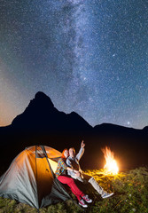 Night camping. Pair of hikers sitting near tent and campfire and enjoying incredibly beautiful starry sky in the background silhouette of the mountains. Long exposure