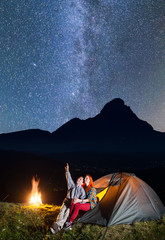 Spoed Foto op Canvas Kamperen Night camping. Romantic family - man and woman sitting near tent and campfire and enjoying incredibly beautiful starry sky in the background silhouette of the mountains and village in the valley