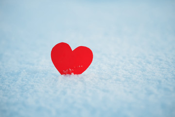greeting card with red lonely heart on the dazzling blue snow