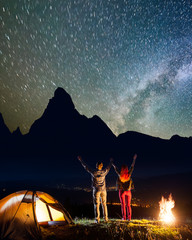 Happy hiker family - man and woman raised their hands up under incredibly beautiful starry sky and Milky way near campfire and tent, looking on the silhouettes of the mountains. Low light