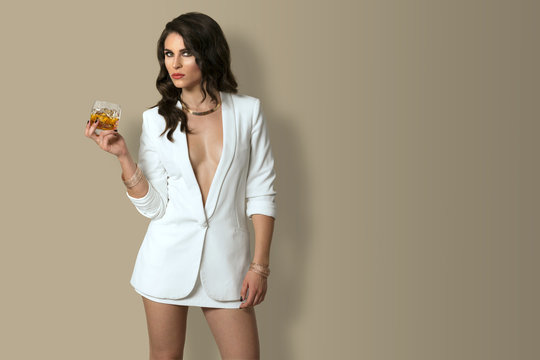 Powerful beautiful sophisticated attractive woman with a cocktail beverage standing confidently