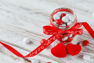 Colorful candy jar decorated with a red bow with hearts on white wooden background. Valentines day concept