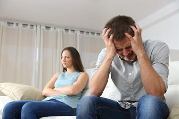Sad man and angry girlfriend at home