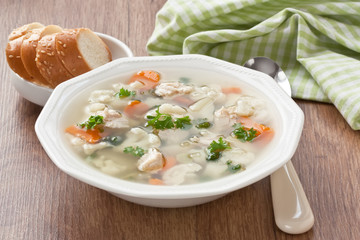 Soup with chicken, cauliflower, vegetable and bread in white plate / Vegetable soup with chicken, cauliflower, carrot, potato, green peas, parsley and slice white bread in plate on wooden background