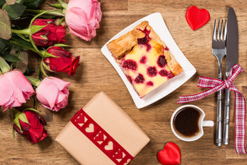 Raspberry cake on white plate, red hearts, coffee and roses on wooden background. Valentines Day background