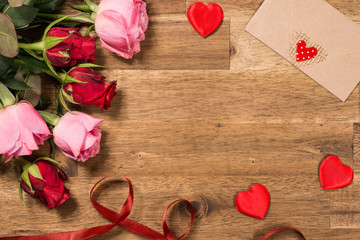 Roses, red hearts and greeting card on wooden background. Valentines day background