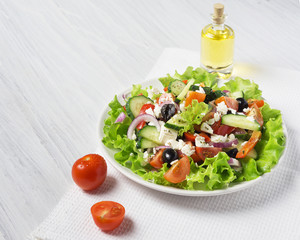 Fresh vegetable Greek salad with oil bottle, top view