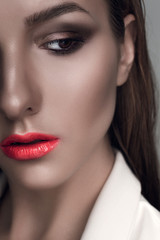 Portrait of a beautiful woman with creative make-up coral lips in white jacket smooth and wet hair
