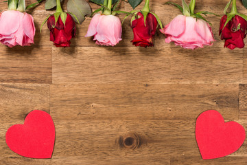 Frame with Roses and red hearts  on wooden background. Valentines day background