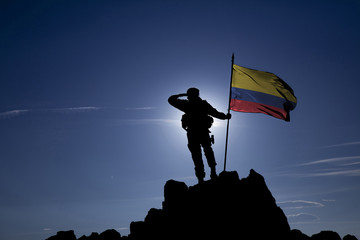 Soldier on top of the mountain with the Colombian flag