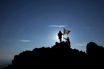 Two soldiers raise the Mexican flag on a mountain top