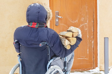 Disabled man on wheelchair near door with firewood logs