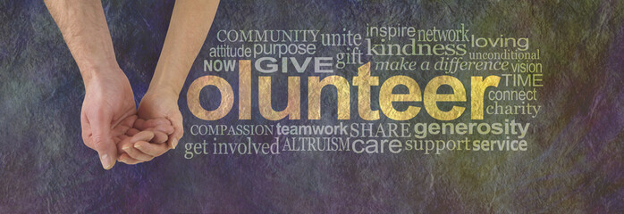 We can volunteer together - male hand cupped by a female hand making the V of VOLUNTEER surrounded by a word cloud on a rustic dark colored stone effect background