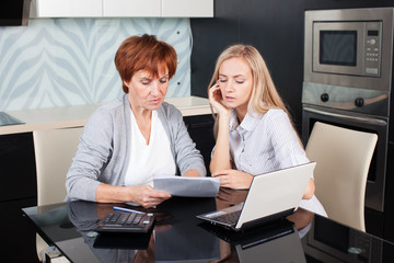 Two women discussing documents at home