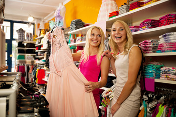 Shopping in clothes store - Two cute women in clothing shop pick