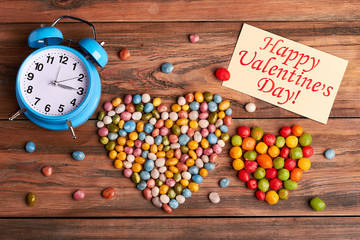 Greeting card and alarm clock. Colorful candies on wooden surface. Time to celebrate Valentine's Day.