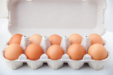 Ten dozen hen eggs in a paper container on a white background