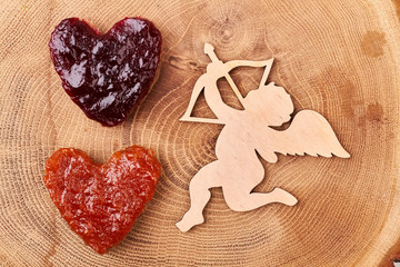 Cupid near heart-shaped jelly bread. Toast with jam on wood. Cupid's symbolism in culture.