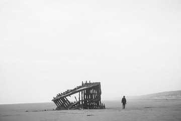 A man walks past a shipwreck on the beach at Fort Stevens State Park in Oregon