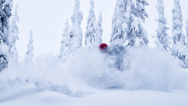 Male snowboarder making powder turn in the backcountry