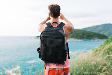 Nothing is more beautiful than this view. Young man with backpack taking a picture of the view over the ocean